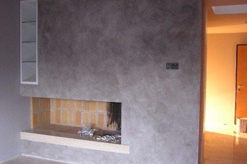 Parete dipinta di grigio intorno al caminetto con effetto marmo
