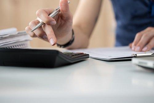 una mano con una penna che sta premendo con le dita i tasti di una calcolatrice