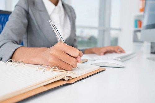una mano con una penna che scrive su un' agenda
