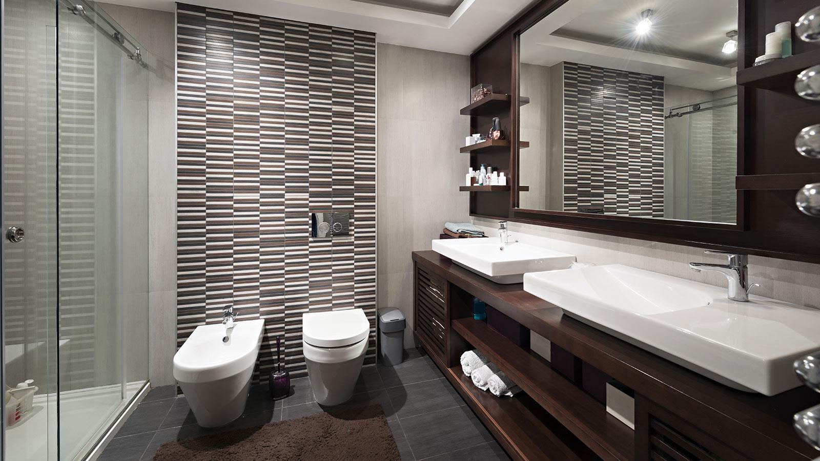 Un bagno grande con una box doccia sulla sinistra, un Wc, un bidet al centro e sulla destra un mobile di legno con un specchio grande e delle mensole con asciugamani, candele e cosmetici