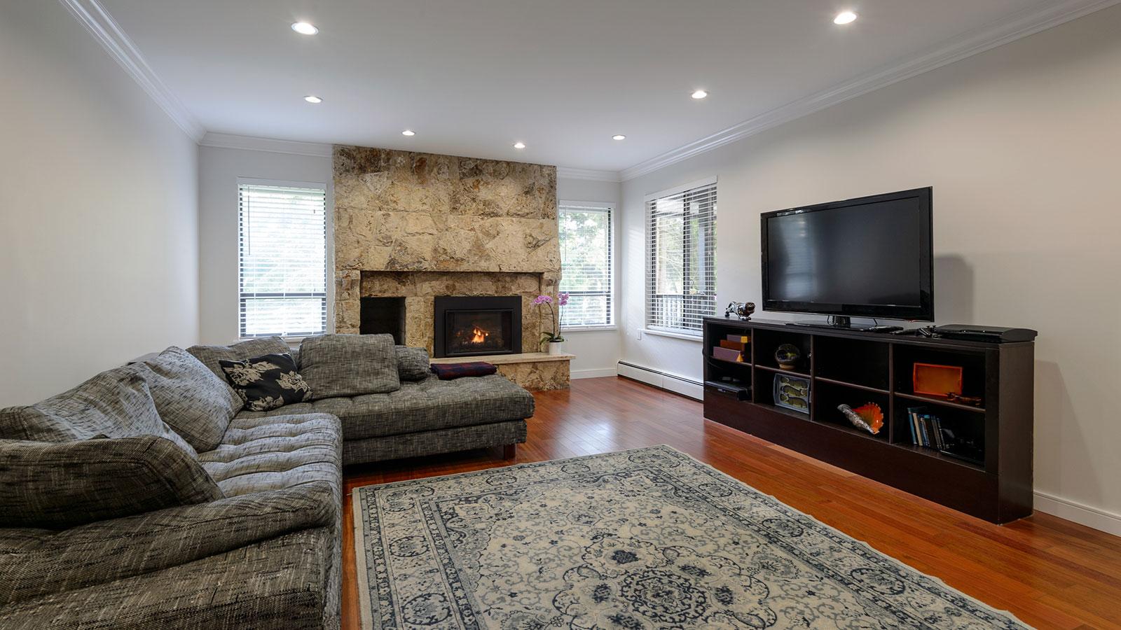 Un divano angolare di color grigio, un mobile Tv davanti e sulla sinistra un camino