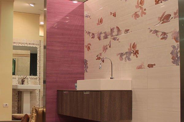 Un lavabo un mobile di color marrone sotto e muri con delle piastrelle di color rosa