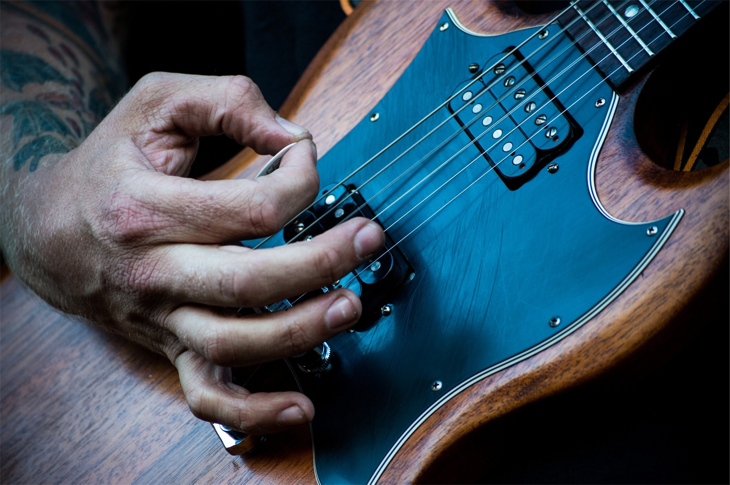 A close up of a person strumming an electric guitar