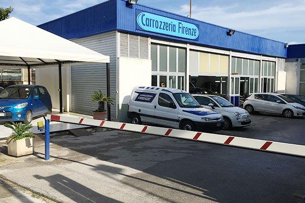 delle macchine parcheggiate fuori dalla carrozzeria e l'insegna con scritto Carrozzeria Firenze
