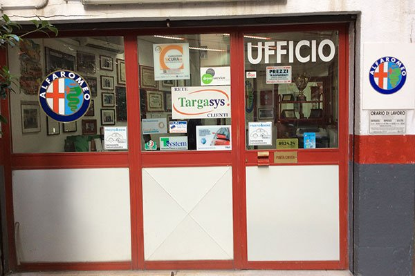 porta d'entrata in vetro con il logo Alfa Romeo e la scritta Ufficio