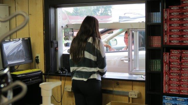 clerk serving a customer at our 24/7 drive through smoke shop