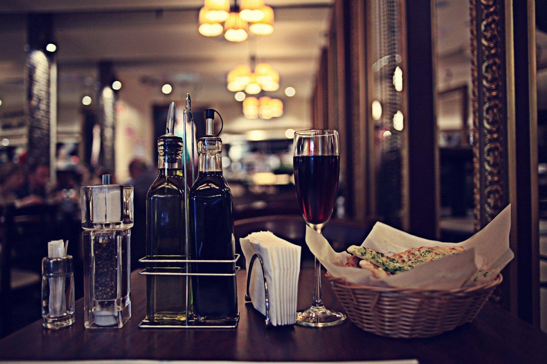 Tavola apparecchiata con antipasto, vino in calice, olio, aceto e spezie
