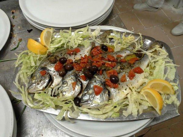 un vassoio con insalata,delle orate,pomodori e olive nere