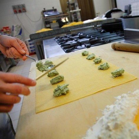 due mani di un uomo che preparano dei ravioli freschi