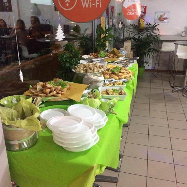 Un buffet con tovaglie verdi e degli antipasti