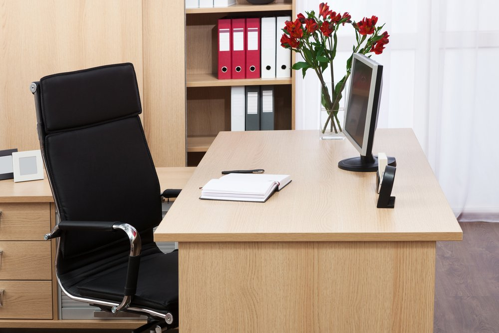 Office space with wooden desk and black chair