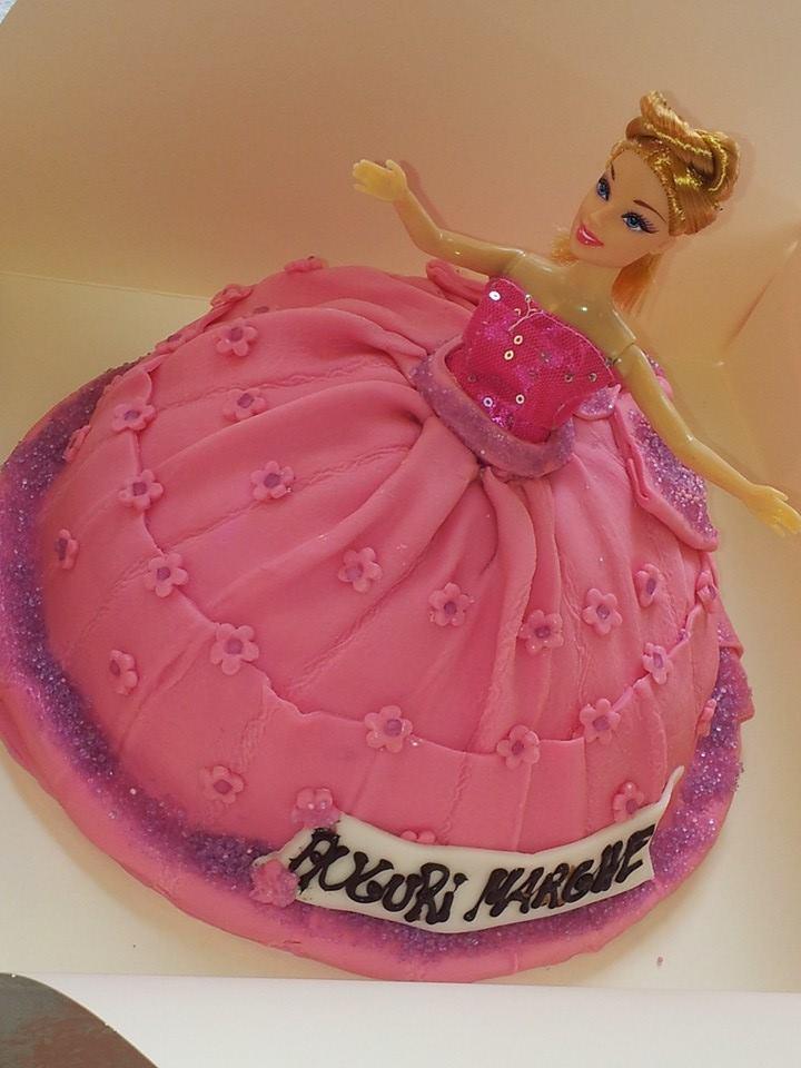 una torta a forma di barbie con una gonna di glassa fucsia e la scritta Auguri Marghe