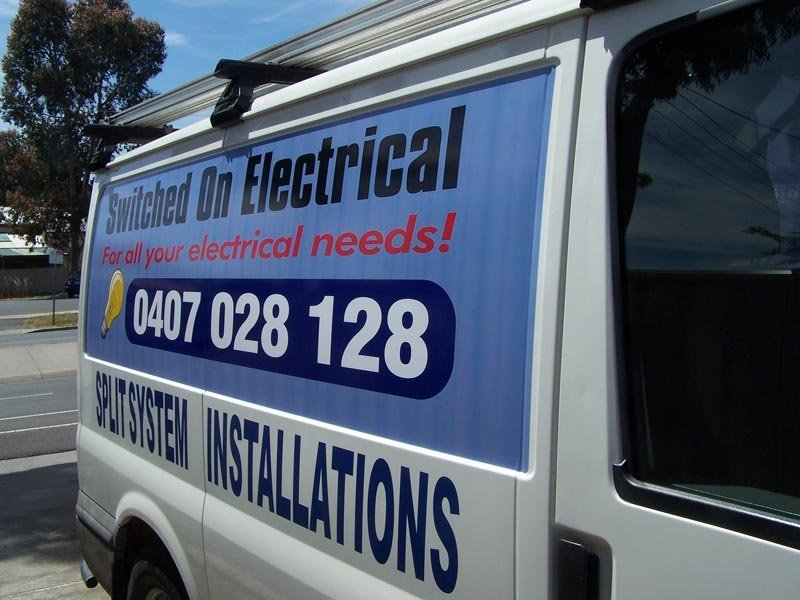 switched on electrical sign on side of van
