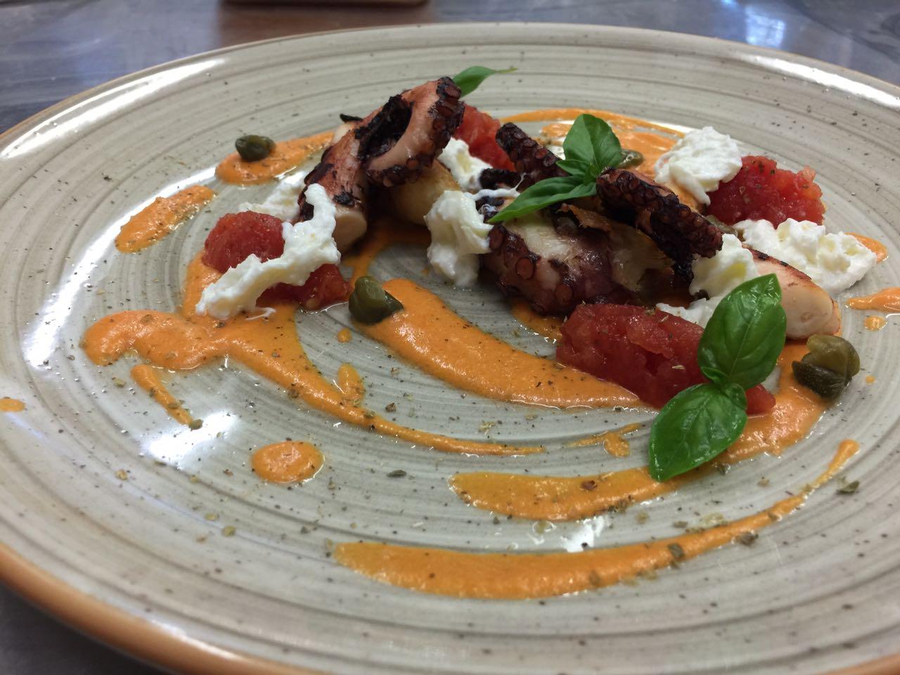 Piatto di carne guarnito con basilico, pomodoro e salsa rossa