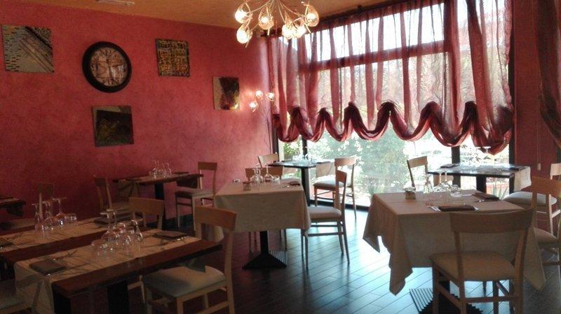 interno del ristorante con tavoli bianchi e tende rosse