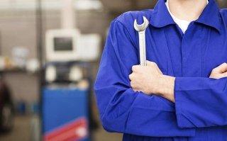 un meccanico che tiene in mano una chiave inglese