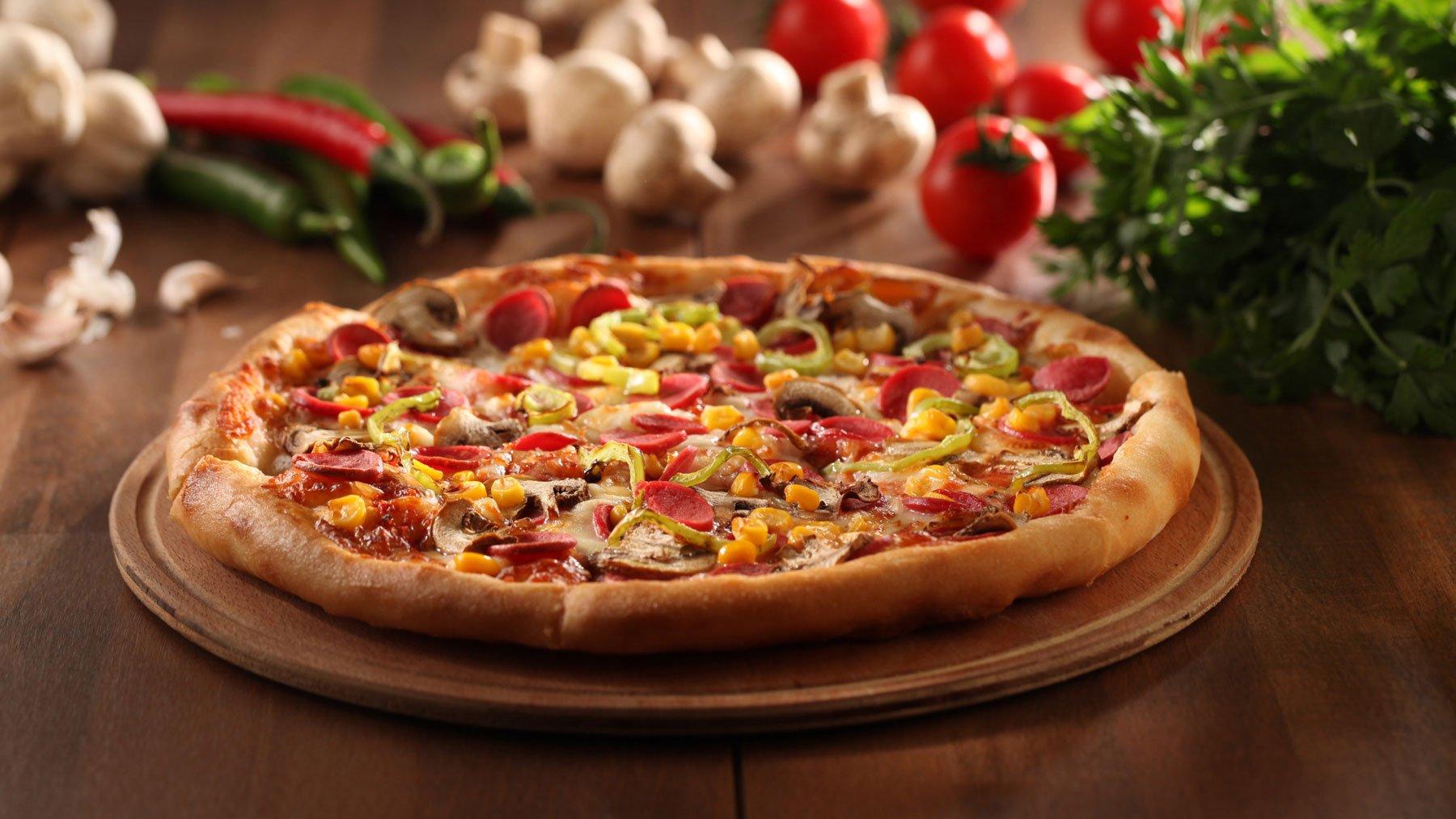 Tagliere di pizza con mais, wurstel , funghi e peperoni verdi a Sarzana (SP)