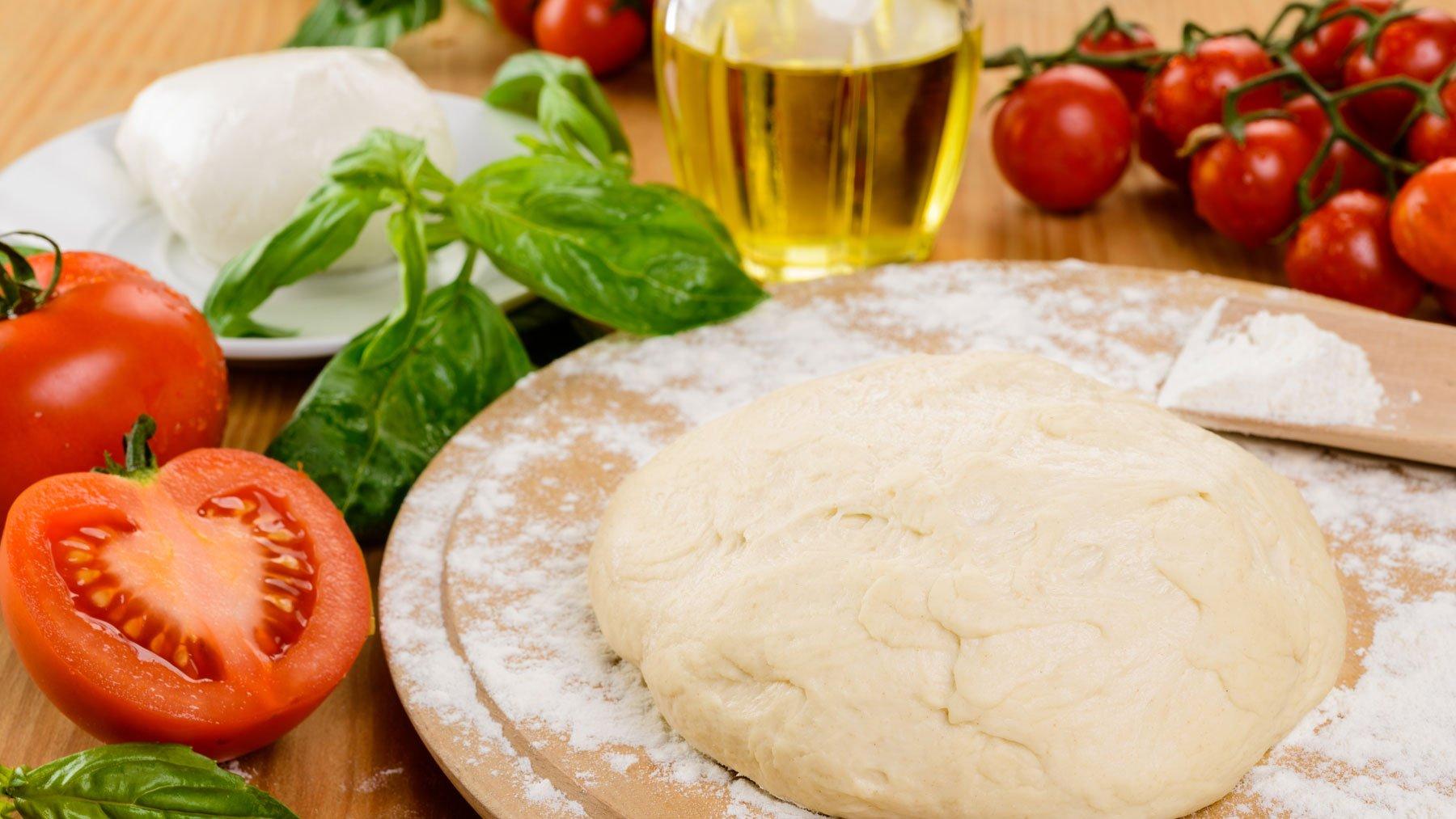 Tagliere con impasto lievitato, olio di oliva, pomodorini e mozzarella a Sarzana, SP
