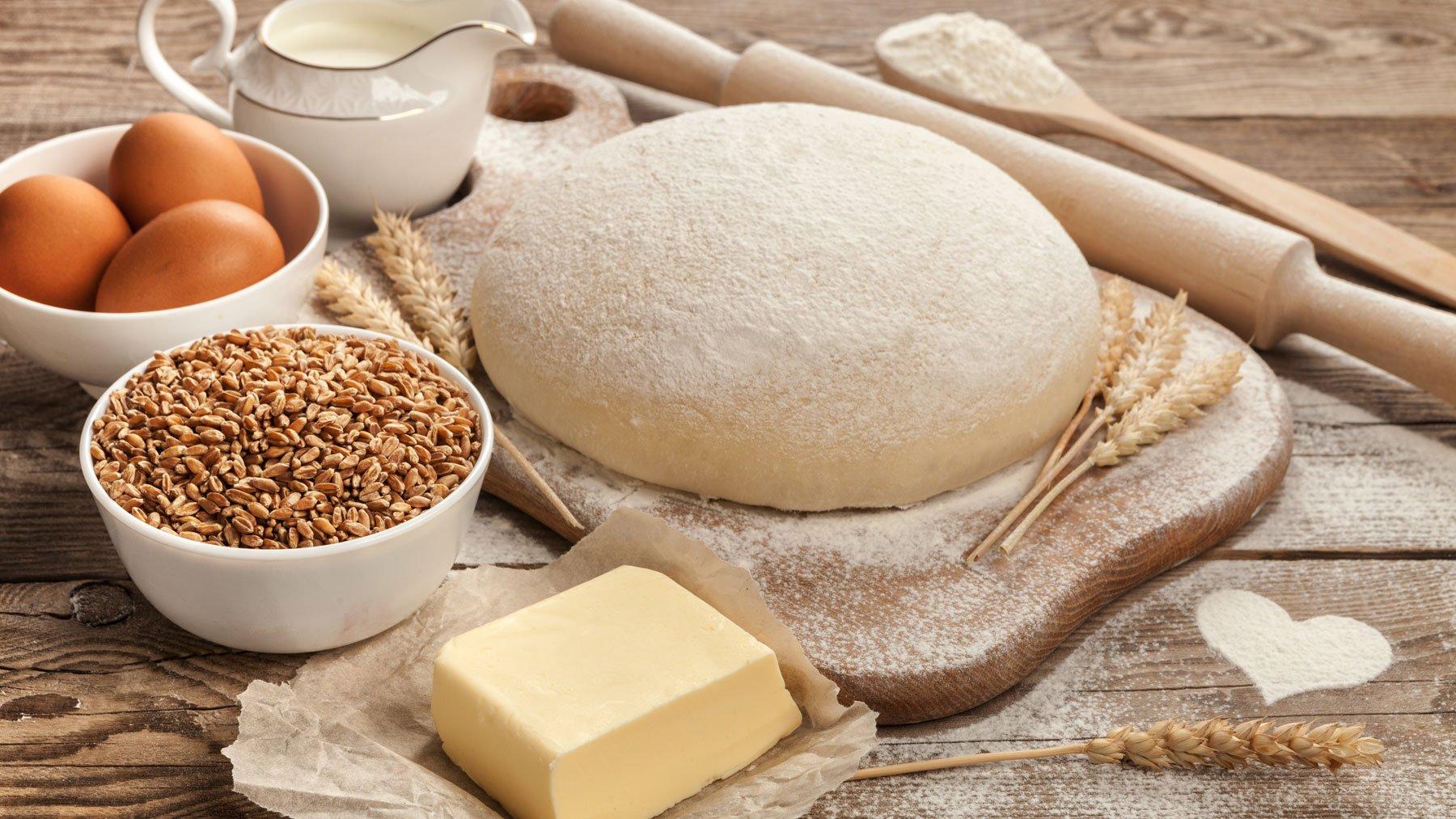 Piano di lavoro con impasto, uova, latte, burro, mattarello e cucchiaio in legno a Sarzana (SP)