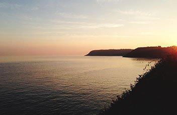 Cliffs over a calm sea against a pale gold sky