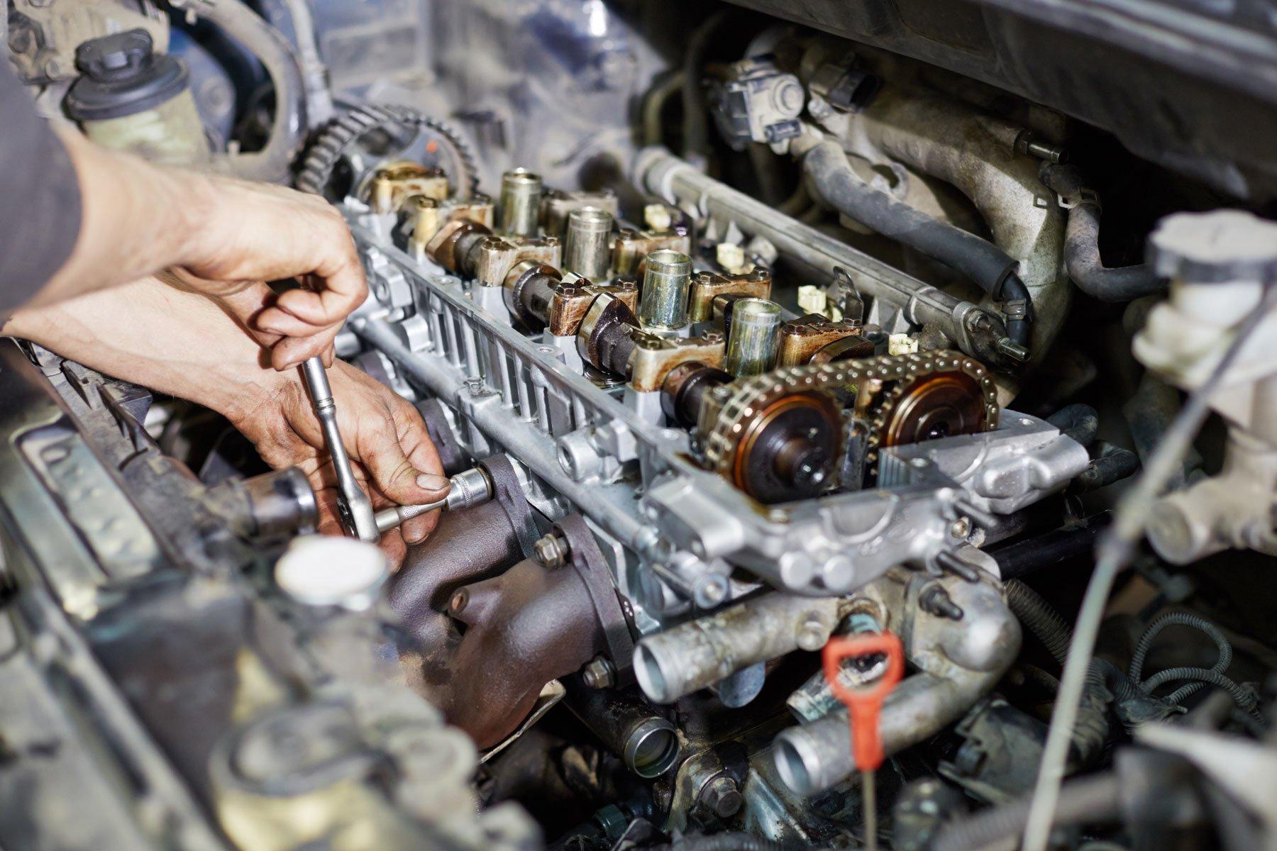 Meccanico sta avvitando una vite di una parte del motore di una vettura