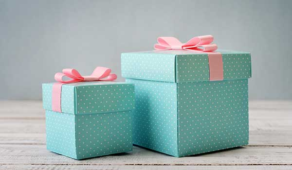 scatole regalo color celeste a puntini bianchi con un nastro rosa