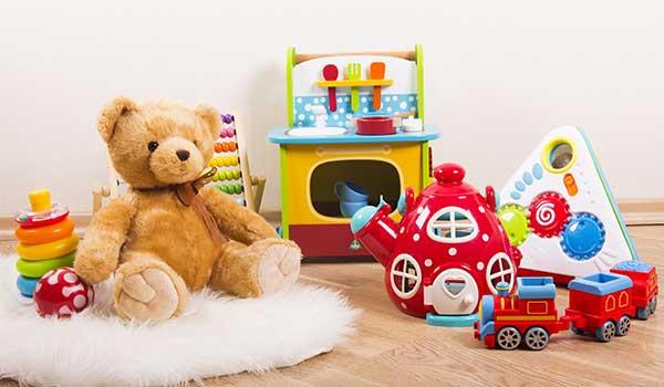 serie di giocattoli per bambini, orsetto di peluche, trenino, una teiera rossa un set da cucina giocattolo, degli anelli e un abaco