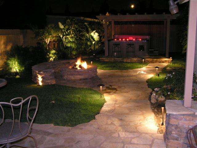 backyard with landscape lighting along a pathway and in trees