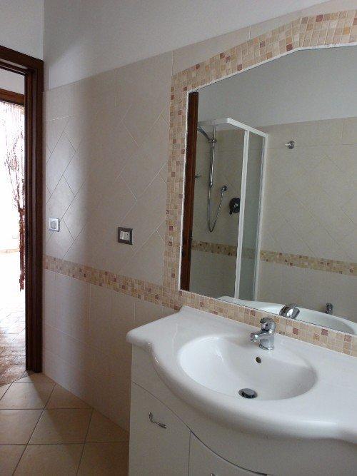 Vista del bagno, parete di piastrelle bianche e  banda di piccole piastrelle di toni bruni