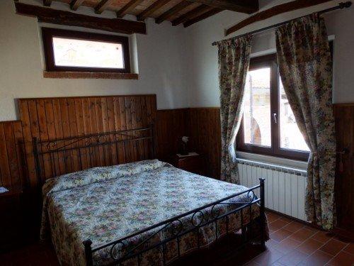 Camera da letto matrimoniale con le parete di legno e le travi a vista