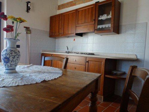 Cucina con i mobili di legno e la parete di piastrelle bianche