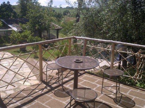 La terrazza con tavola circolare e gli sgabelli di vimini