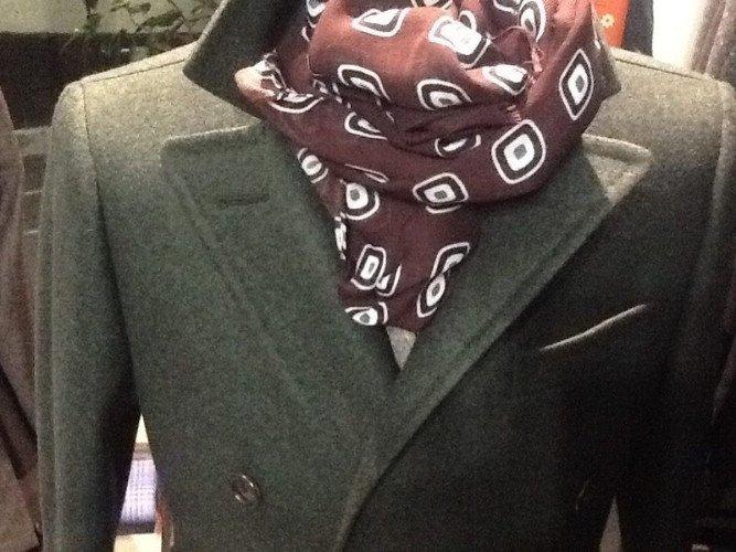 una giacca doppiopetto grigia e un foulard bordeaux a disegni