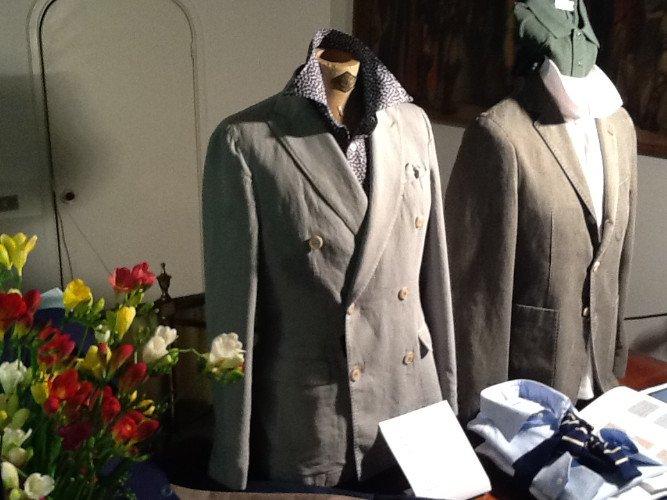 due giacche doppiopetto color beige e accanto un vaso di fiori