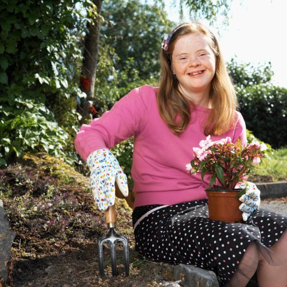 Special needs girl smiles while gardening