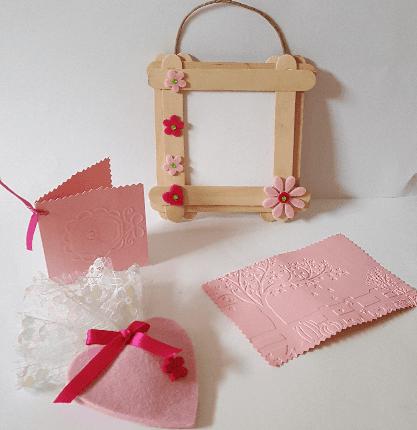 una cornice in legno e dei bigliettini in cuoio rosa