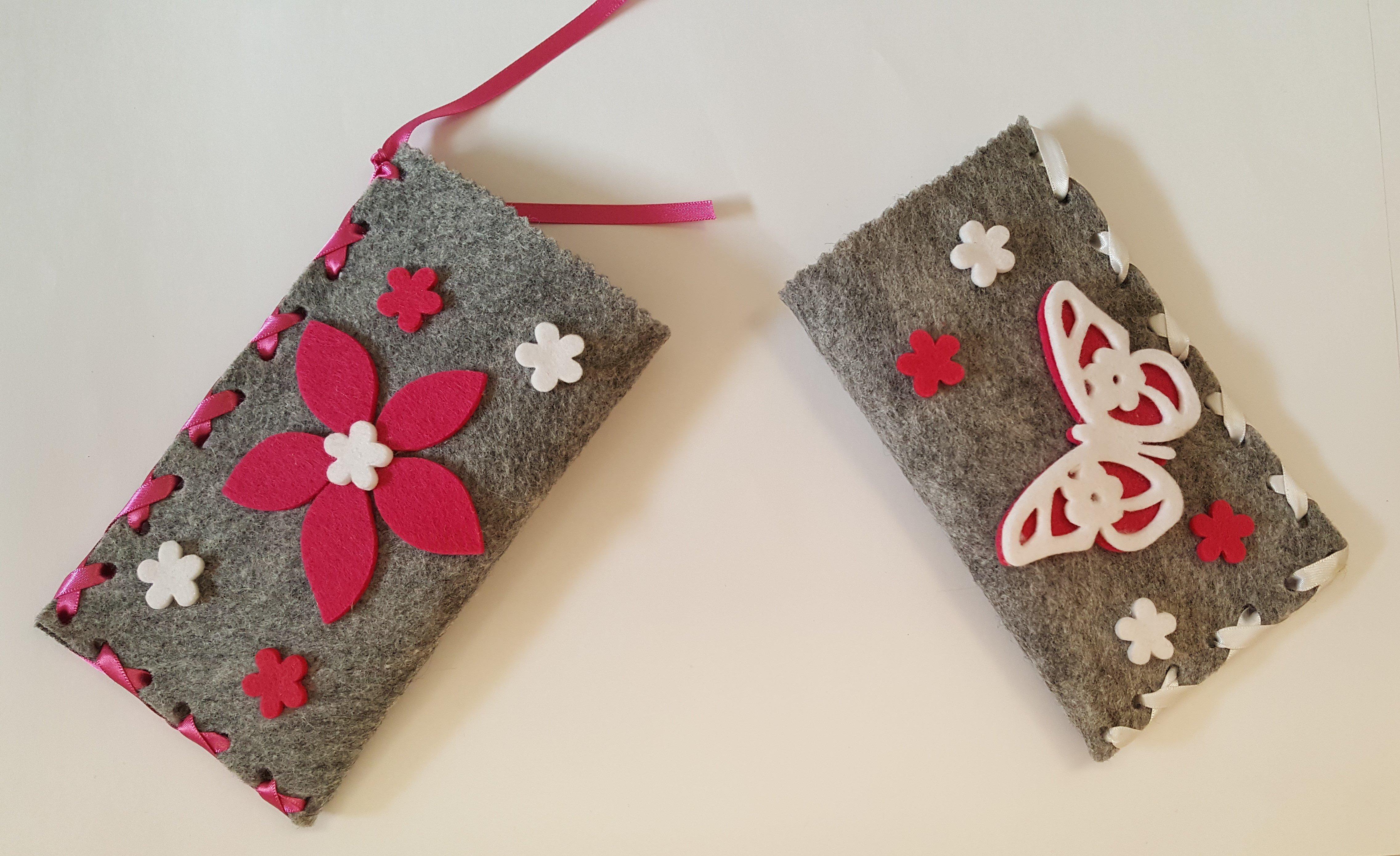 due astucci grigi uno con fiore rosso uno con farfalla bianca