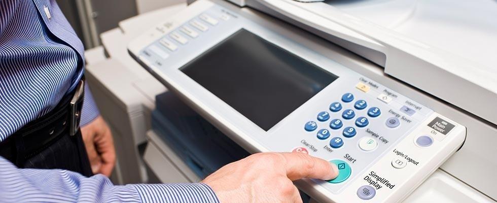 persona spinge bottone di invio su una fotocopiatrice da ufficio