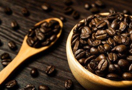 Una ciotola e un cucchiaio pieni di grani di caffè
