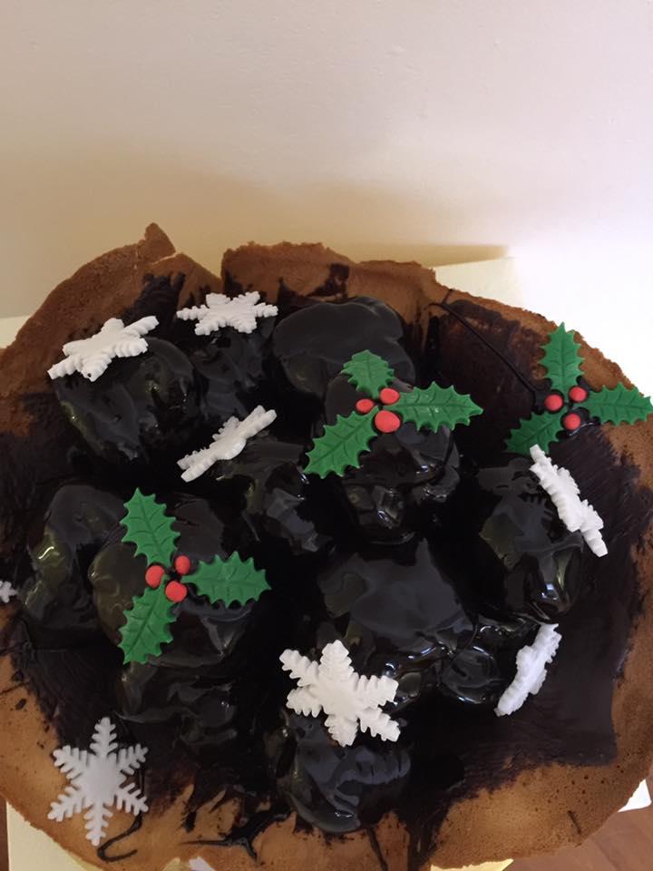 una torta con sciroppo di cioccolato e decorazioni natalizie