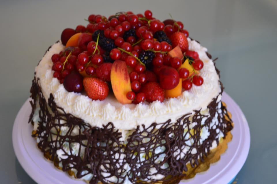 una torta con una rete di cioccolato e dei frutti di bosco