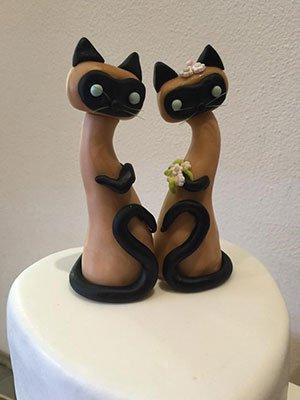 una torta con sopra una forma di due gattini