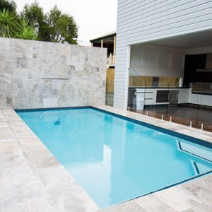 swimming pool with travertine tile feature wall