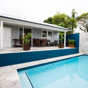in-ground pool with entertaining area, pool house and gym