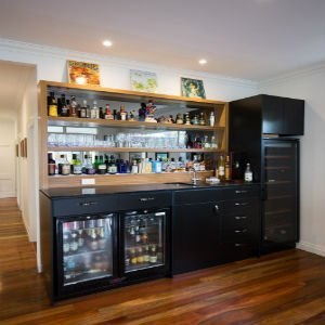built-in bar with timber shelving and black feature cabinetry