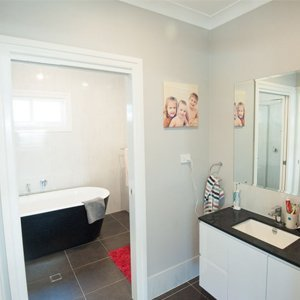 Children's bathroom with separate bath and vanity spaces