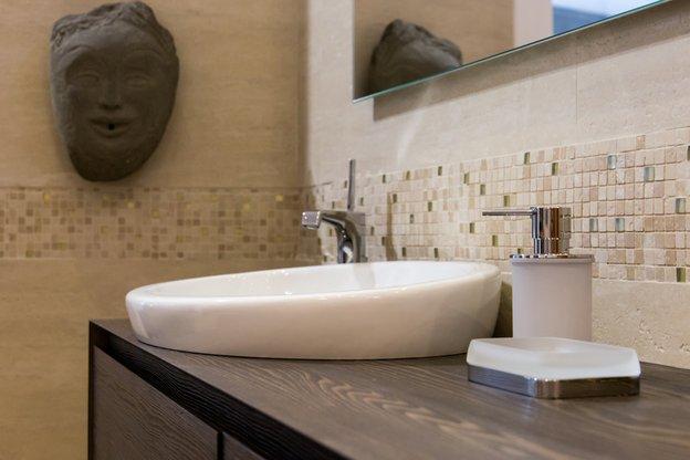 vista angolare di un bagno con scultura in pietra, lavabi con rubinetti e parete in piastralle