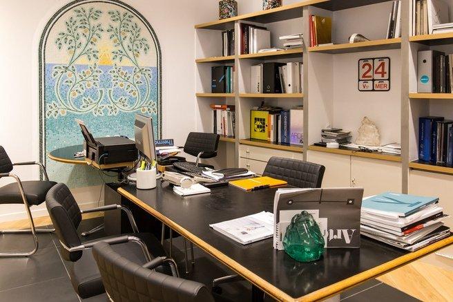 vista interna di un ufficio con oggetti sul tavolo lungo, sedie, libreria a muro e arredamento