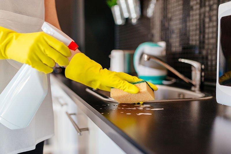 donna mentre pulisce armadi da cucina con pulitore e della spugna