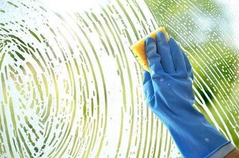 mano con guanto pulisce il vetro